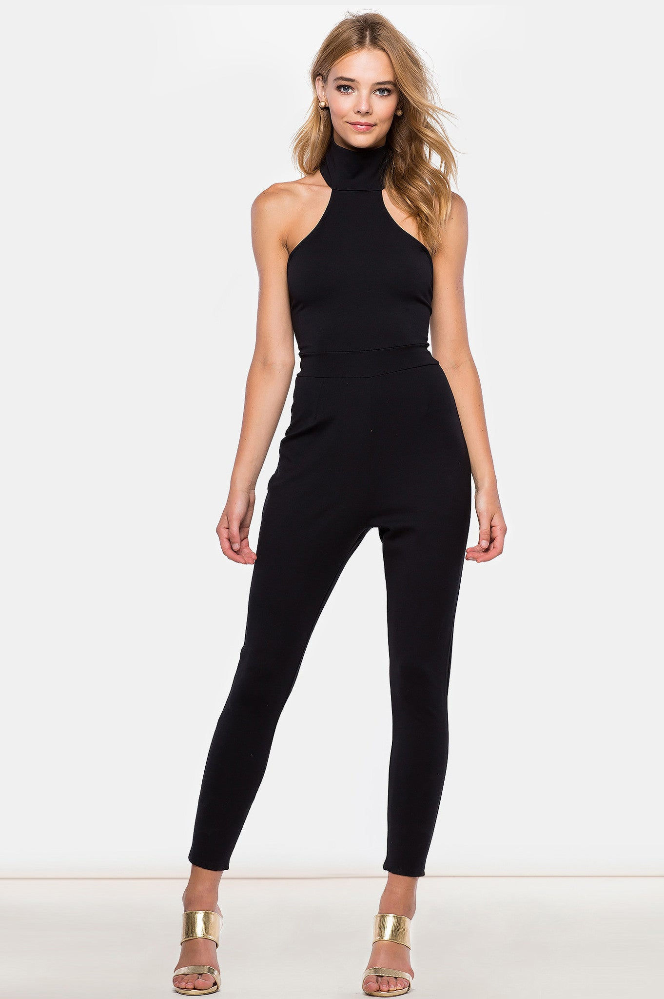 Sleeveless funnel neck turtleneck, open back tapered fitted skinny black jumpsuit, front view.