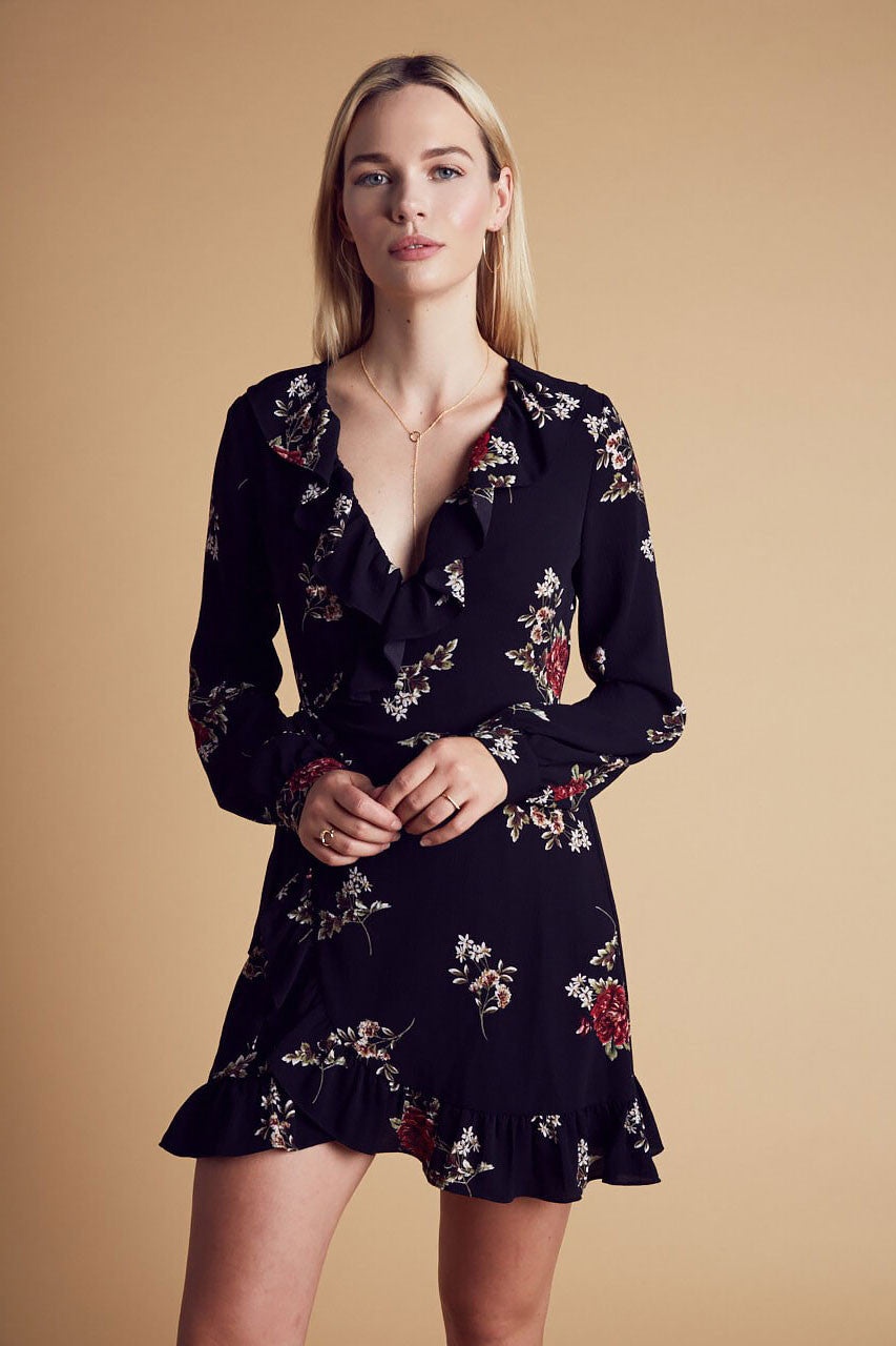 Womens long sleeve black floral print mini wrap dress with ruffles. Front view.
