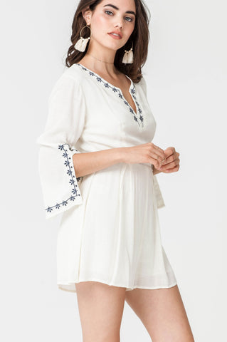 Women's white kaftan romper with blue embroidery trim and 3/4 long sleeves.