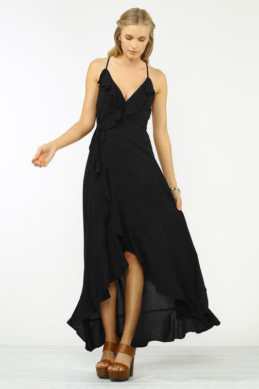 Womens street style party outfit ideas: Long black ruffle trim wrap maxi dress with tassel tie. Front view