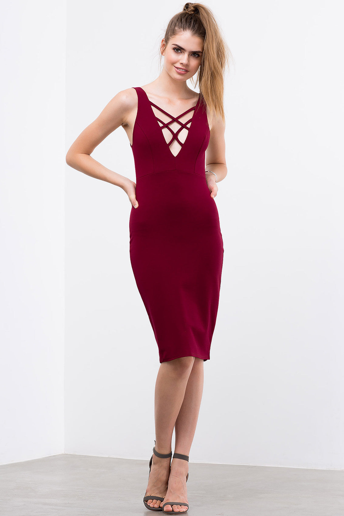 Sleeveless criss cross lace up bodycon midi party dress in burgundy. Front view