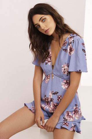 Womens short flutter sleeve romper playsuit with light purlple floral prints for going out.