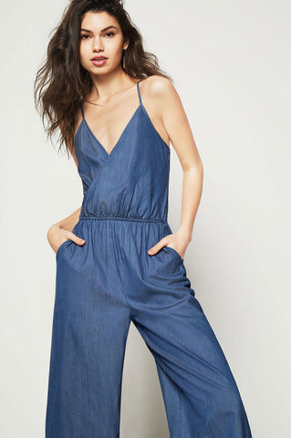 Women's sleeveless medium wash blue denim cropped jumpsuit with surplice v neck and elastic waist. Casual
