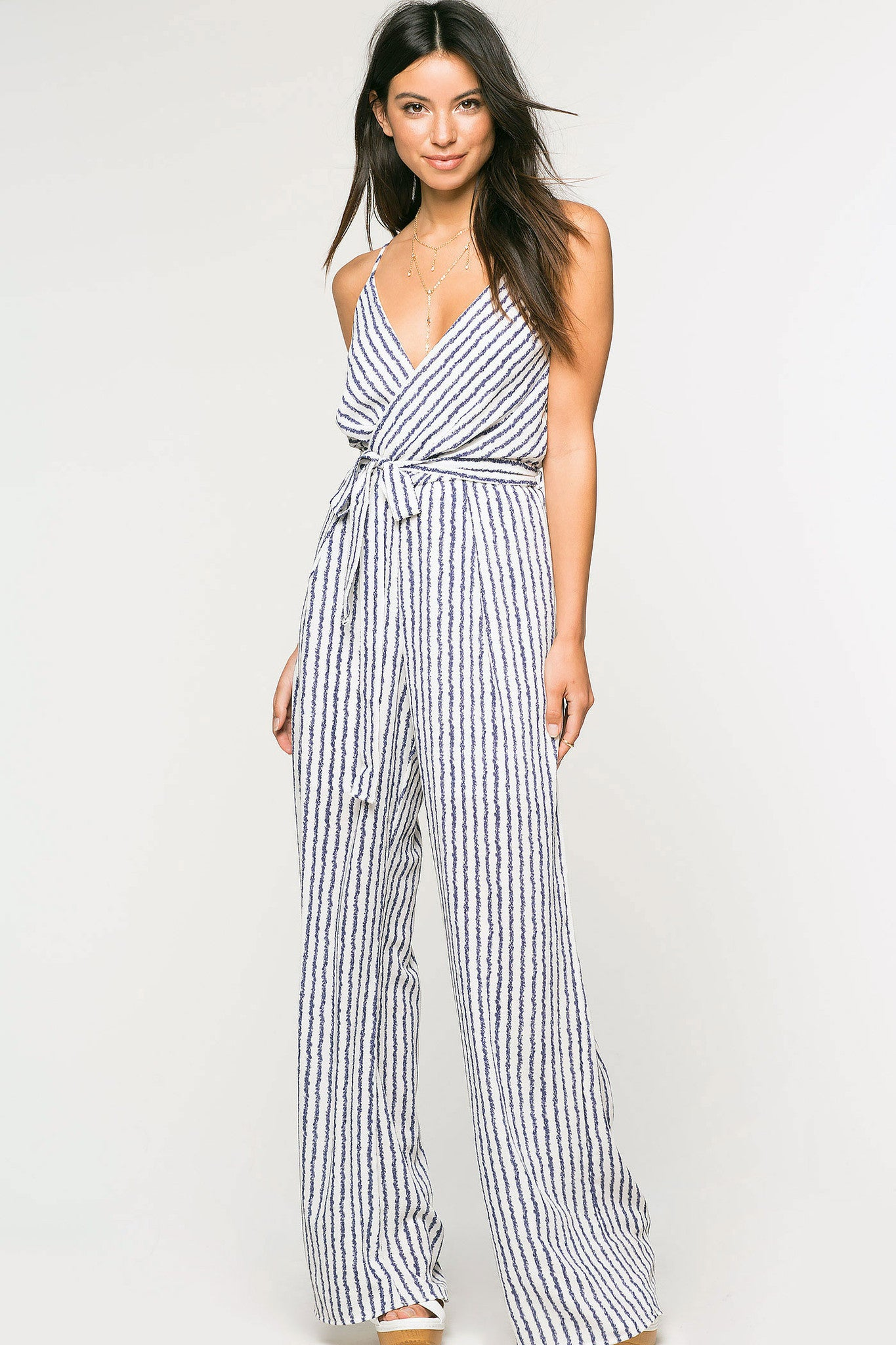 Women's sleeveless blue and white pinstripe stripe surplice wrap deep v-neck jumpsuit with wide legs