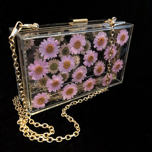 A PERSPEX CLUTCH WITH REAL DAISIES