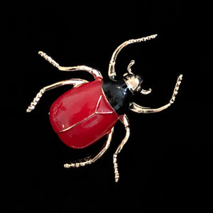 A RED AND BLACK ENAMELLED BEETLE BROOCH