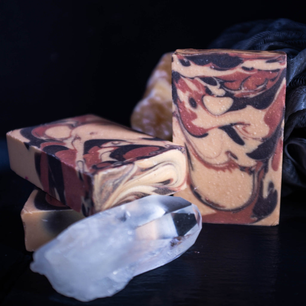 gold bronze copper colored swirl soap with quartz crystal in foreground