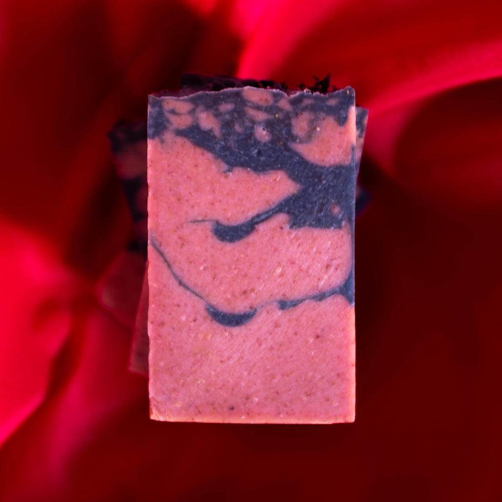 pink soap with black swirls on a red cloth