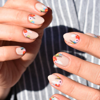 Hello Birdie Nail Art on two hands with nude base and multicolored floral nail art on each nail.