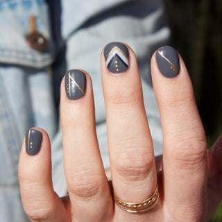 Hello Birdie Nail Art on one hand with grey base and gold and grey geometric accents on each nail.