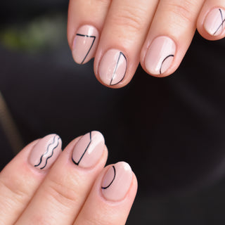 Two hands with Hello Birdie Nail Art with nude base and line geometric art.