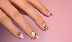 Manicured hand in front of blush background with nail art that has hand painted palm trees on top of daytime abstract squares.