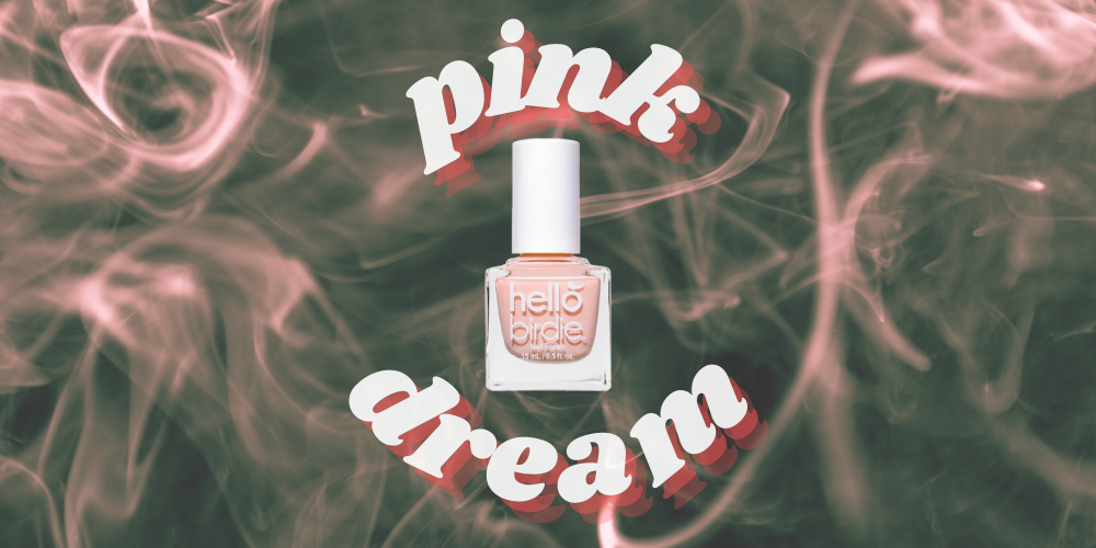 """Hello Birdie classic pastel peach pink polish in a transparent glass square bottle with round white lid, against a smoky pink and gray background, encircled with """"pink dream"""" echoed text"""