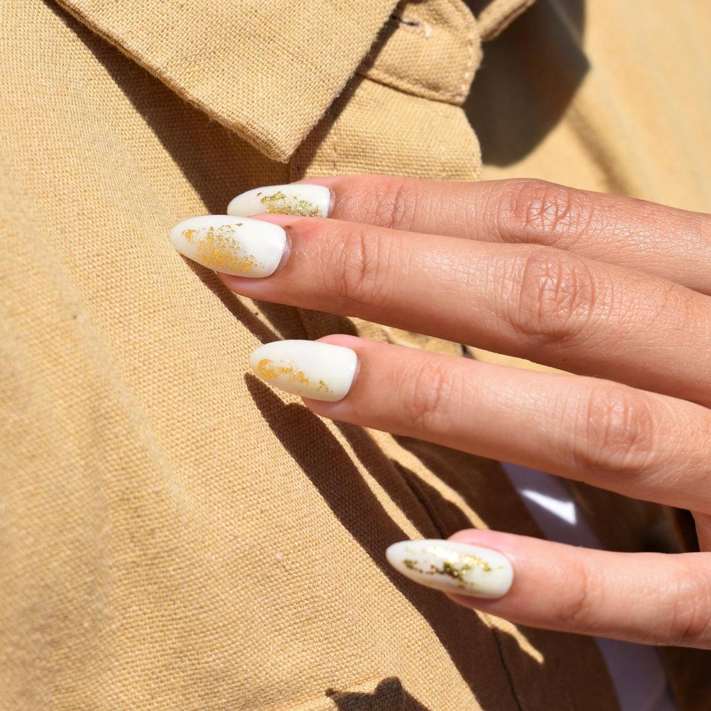 Hand-painted gel polish nail art press-ons.  Gold foil accents on an off-white base with a glossy finish creates a polished look.  One had is pictured and the model is wearing a muted marigold button up shirt behind her hand.