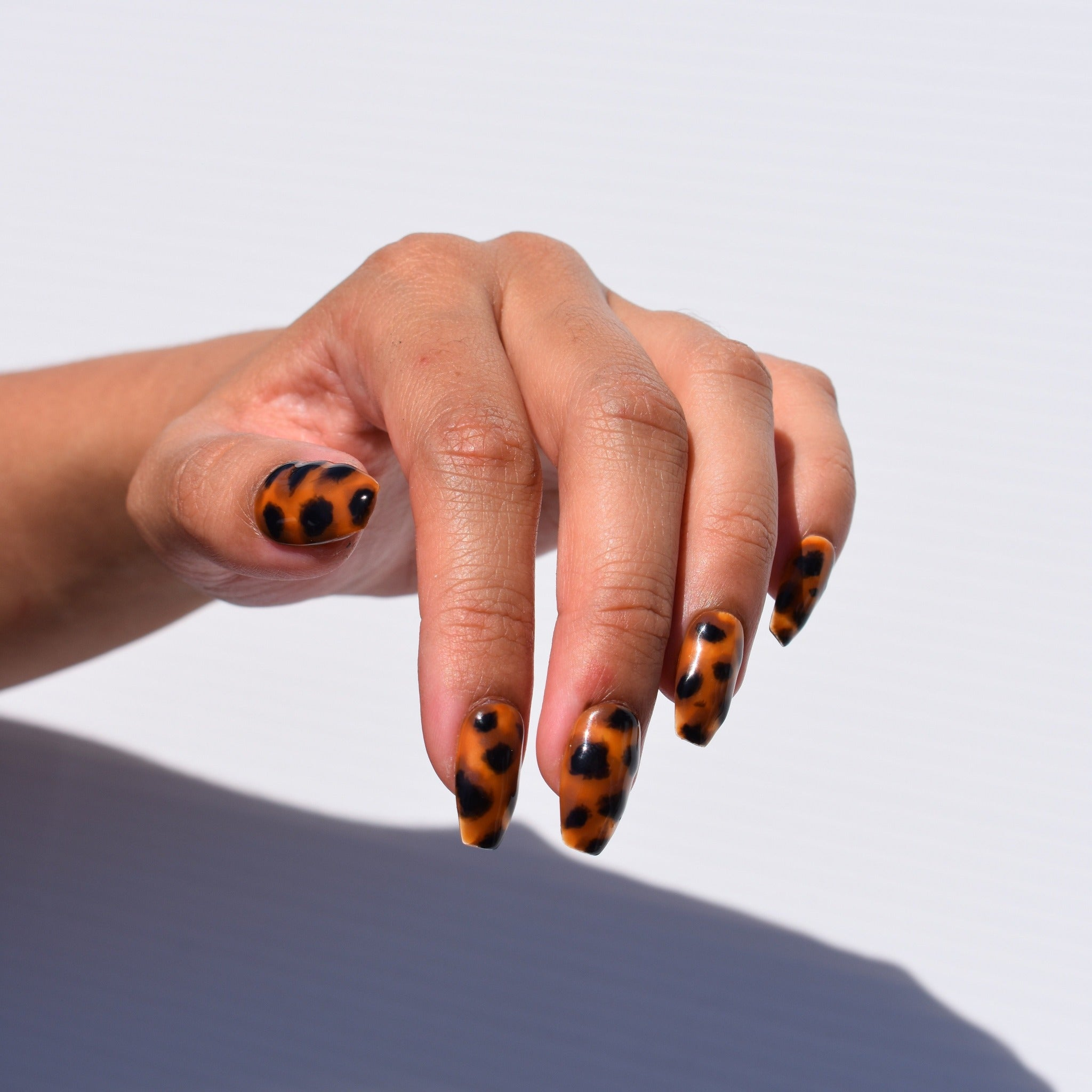 Coffin-shaped hand-painted gel polish nail art press-ons.  Tortoise shell nail art with a glossy finish.  One hand is pictured with a bright white background.
