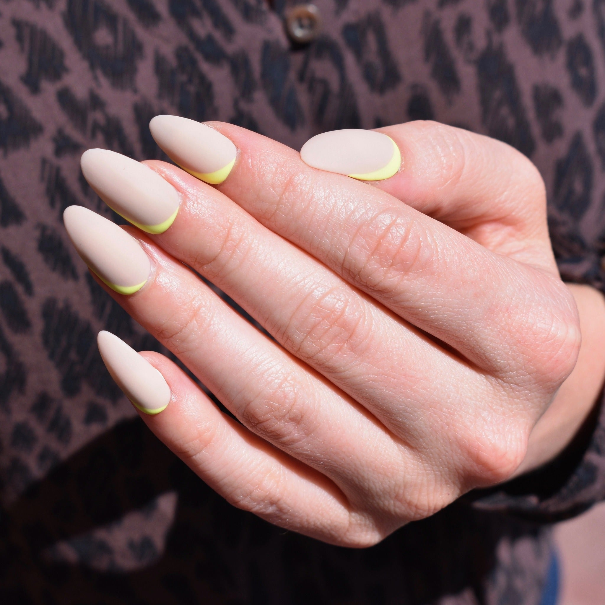 Hand-painted gel polish nail art press-ons.  Neon yellow off-centered accents swiped on the base of each nail and up one side.   Sand colored base with a fresh matte finish.  One had is pictured and the model is wearing a chocolate brown leopard print  button up shirt behind her hand.