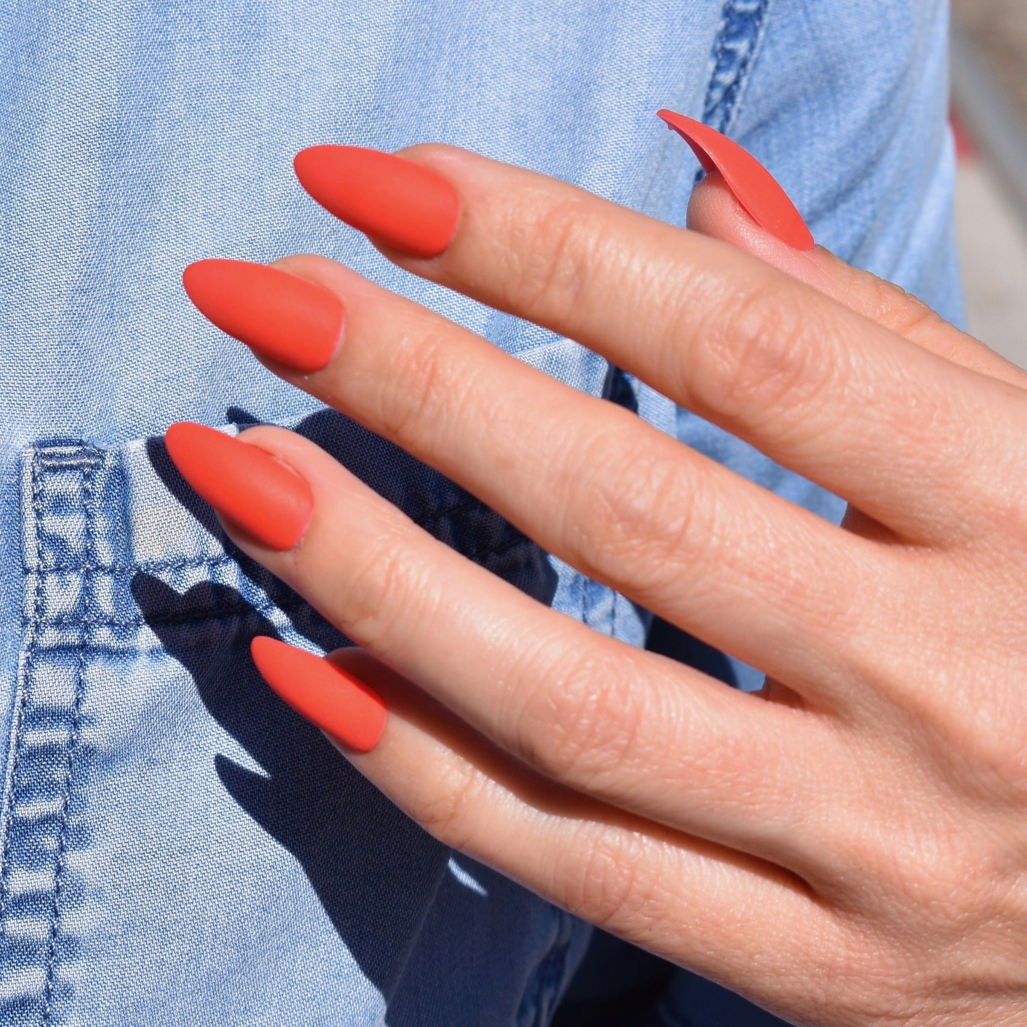 Gel polish hand-painted press on nails on one had. The almond shaped nails are in a vibrant and bright orange with a matte finish. The models hand rests over a denim shirt.