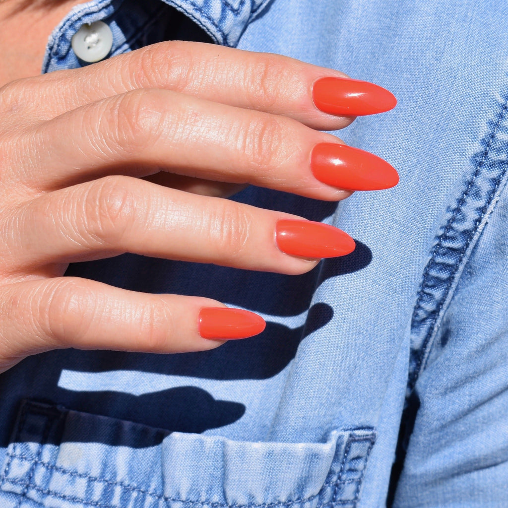 Gel polish hand-painted press on nails on one had. The almond shaped nails are in a vibrant and bright orange with a hi-gloss finish. The models hand rests over a denim shirt.
