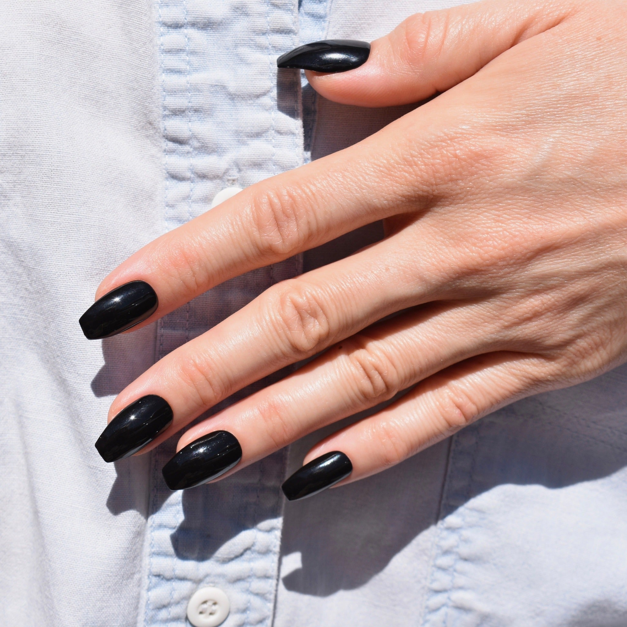 Gel polish hand painted press on nails with nail art on one had.  The Coffin shaped nails are in a black gloss finish.  The models hand rests over a pale denim shirt with white buttons for an effortlessly stylish look.