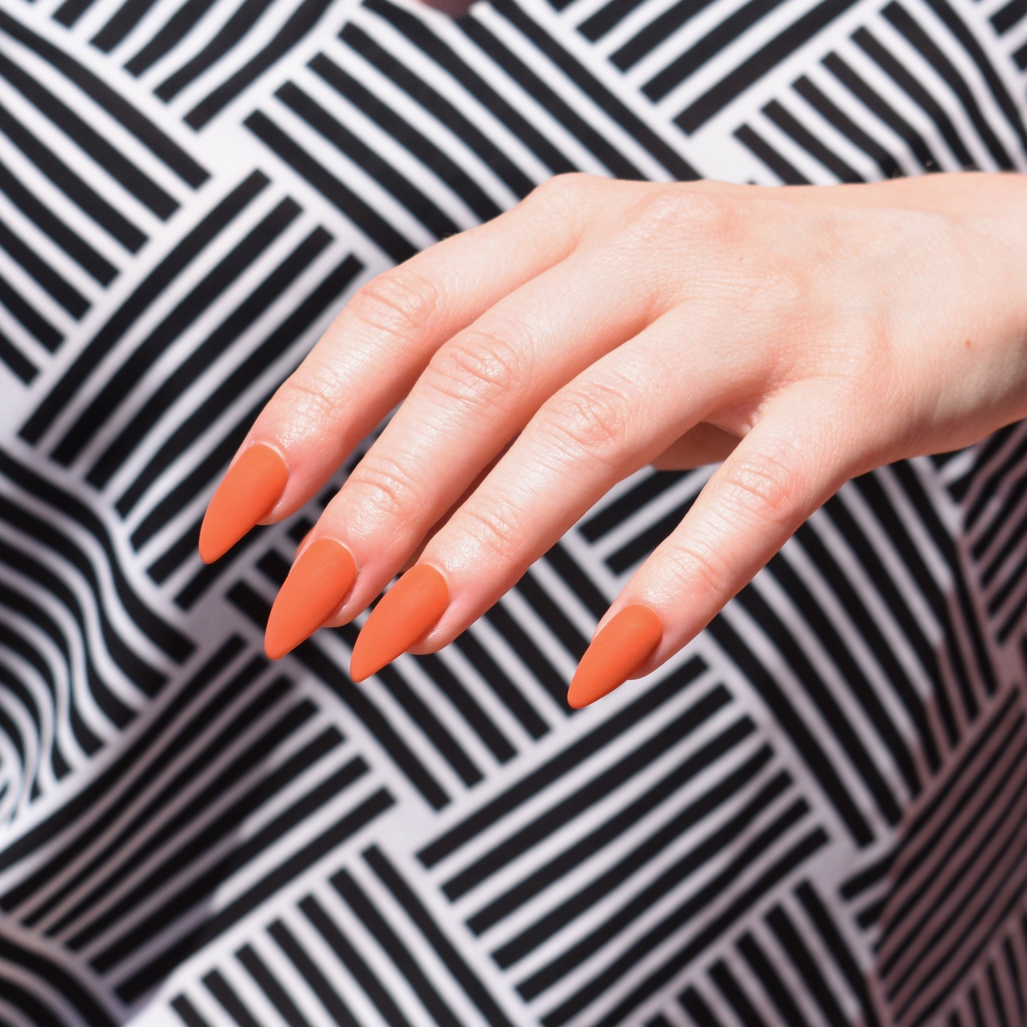 Hand-painted gel polish press-ons in a burnt orange almond shaped matte finish. One hand is pictured and the model is wearing a black and white geometric patterned blouse.