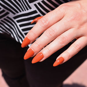 Hand-painted gel polish press-ons in a burnt orange  almond shaped glossy finish.  One hand is pictured and the model is wearing a black and white geometric patterned blouse and black pants.