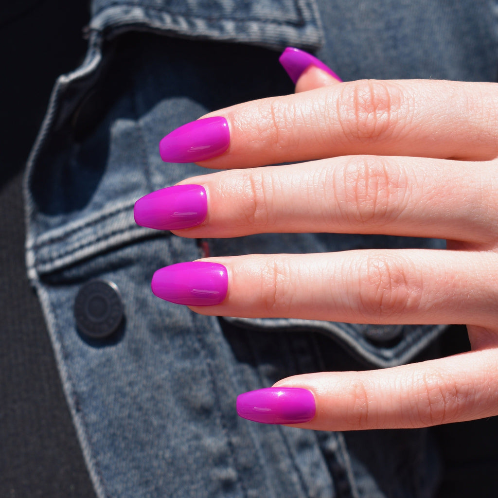 Gel polish hand-painted press on nails on one had. The Coffin shaped nails are in a vibrant fuschia with a hi-gloss finish. The models hand rests over a dark denim jacket and black shirt.