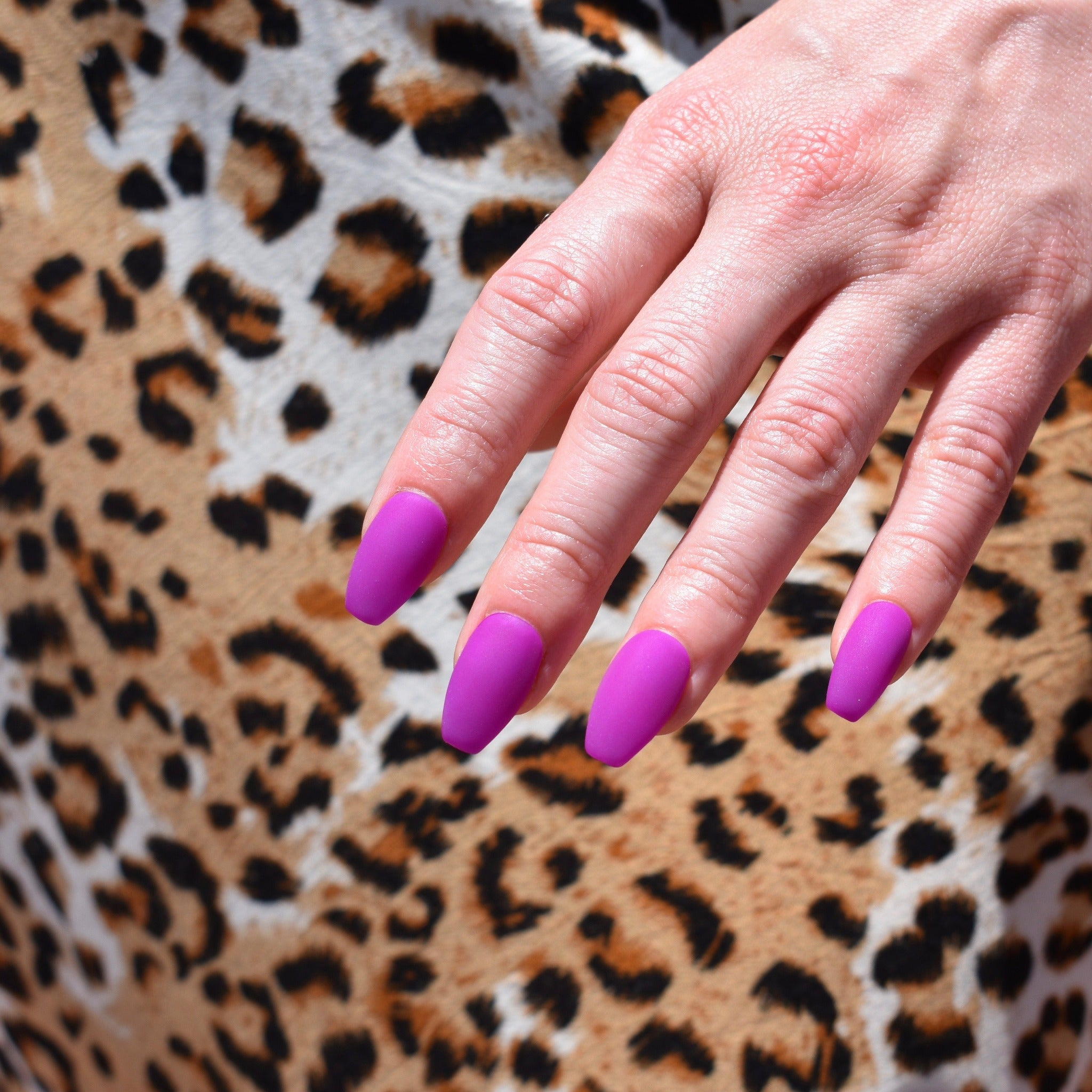 Gel polish hand-painted press on nails on one had. The Coffin shaped nails are in a vibrant fuschia with a matte finish. The models hand rests over a leopard print shirt.