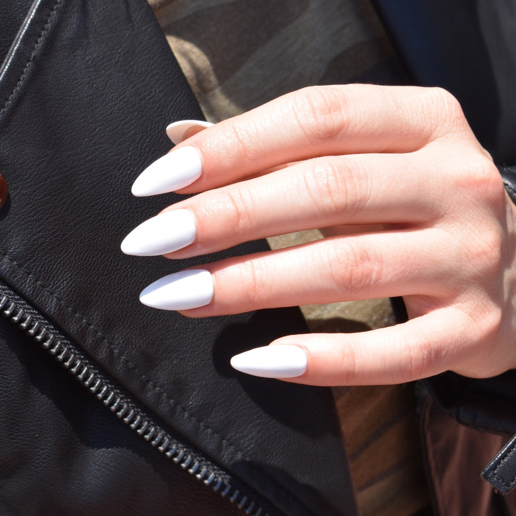 Almond shaped hand-painted gel polish press-ons in a white gloss finish.  One had is pictured and the model is wearing a black leather jacket and camo print shirt behind her hand.