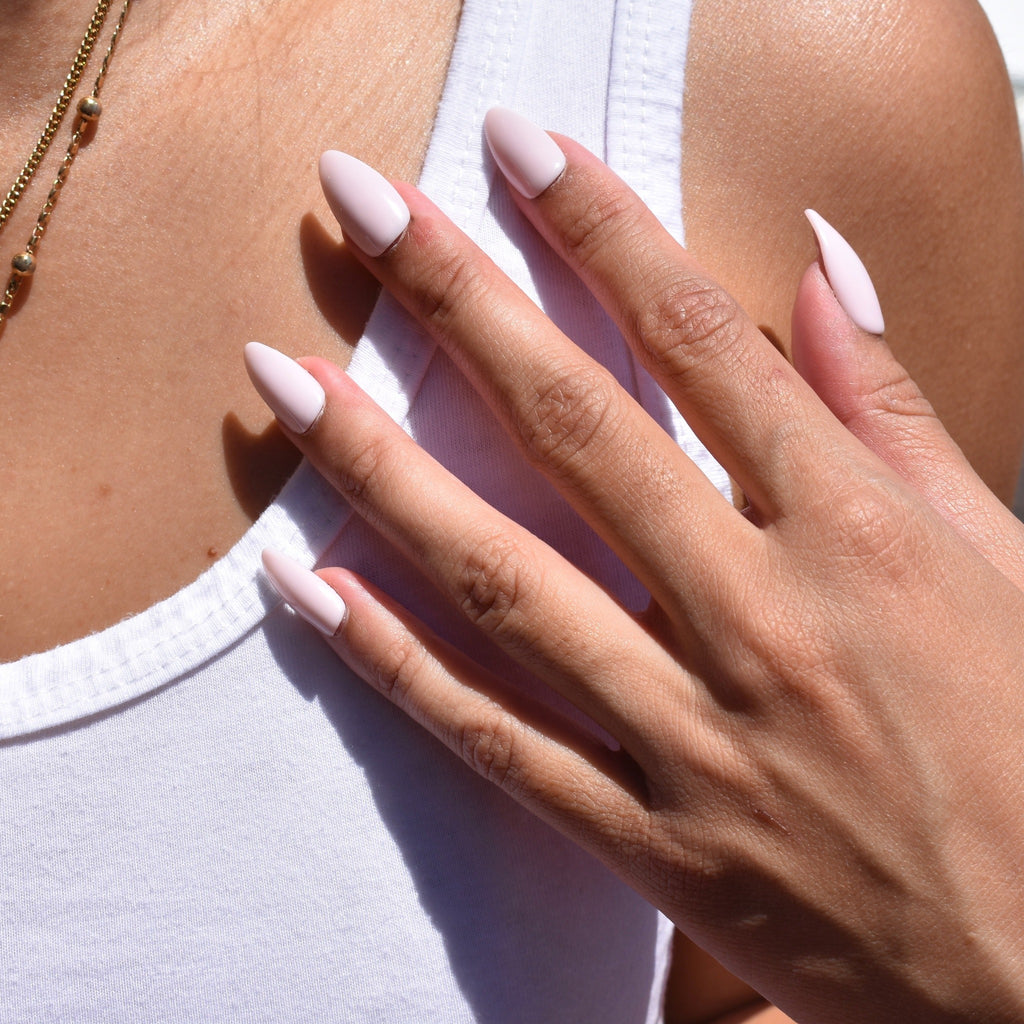 Hand-painted gel polish press-ons in a soft pink glossy finish.  These tips are an almond shape.  The model is resting her one hand over her white tank top. Delicate gold jewelry finishes her sweet and classic look.