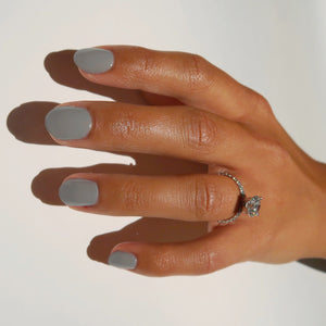 For Flocks Sake is a muted taupe hue, pictured here the single polished hand of a model with squoval shaped nails.  An elegant diamond ring is on her ring finger.  The image is clean and crisp with a white background to support this clean beauty nail polish.