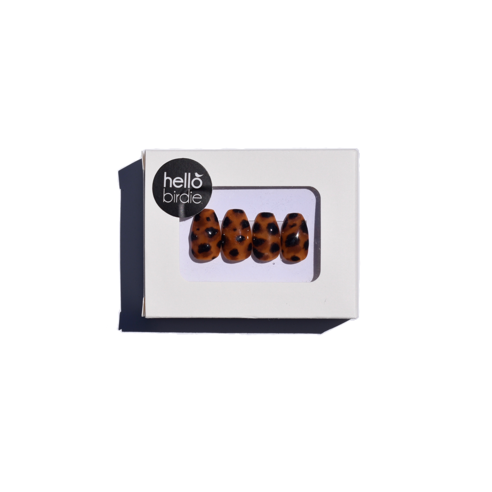 Four press-ons packaged in a rectangular box with a Hello Birdie logo on the top left corner.  A window with rounded corners allows you to view the tortoise shell coffin shaped nails.