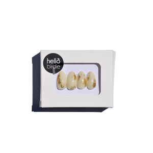 Four press-ons packaged in a rectangular box with a Hello Birdie logo on the top left corner.  A window with rounded corners allows you to view the off-white with gold foil nail designs on each of the nail tips.