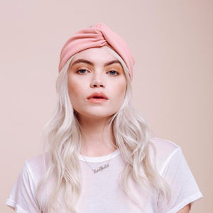 Front view of model wearing Baby Doll pink turban headband