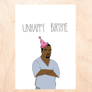 "White background with a cartoon drawing of Kanye West in a grey v-neck tee shirt and a pink cone party hat with his arms crossed and a grumpy facial expression that reads, ""Unhappy Birthye""."