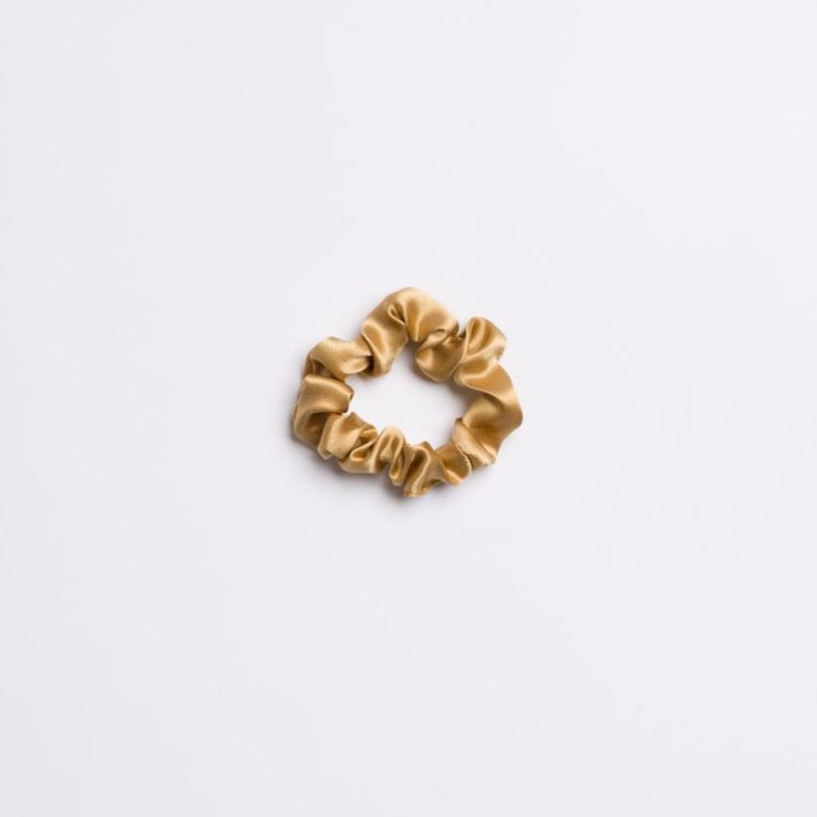 Gold Rush Mini Scrunchie in a light gold color and silk from I'm With the Band laying flat