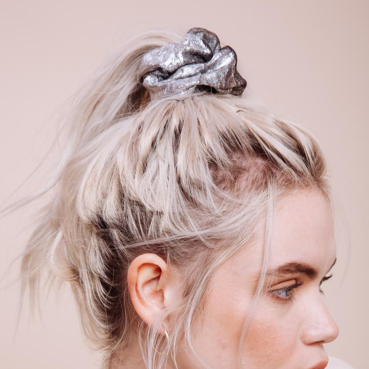 Close up side view of a model wearing a silver Moonage Daydream Scrunchie in a messy ponytail on top of head