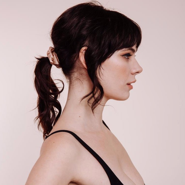 Side view of a model wearing Champagne Supernova Mini Scrunchie which is champagne colored silk