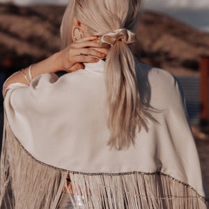 A fashion photo of a model wearing a Cowgirl in the Sand Scrunchie in a low ponytail, a white fringed cape and silver leather skirt in the desert