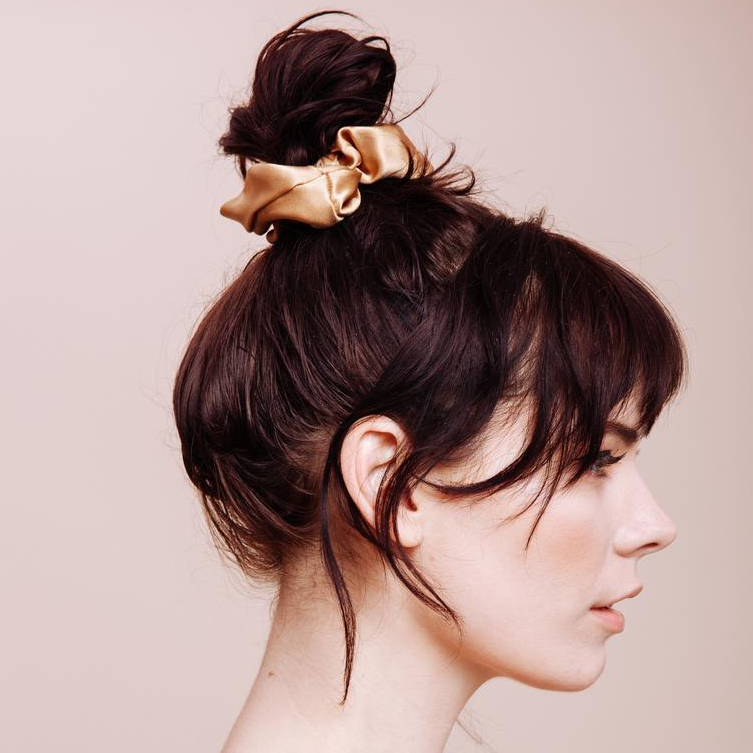 side view close up of a model wearing a Gold Rush Scrunchie in a messy top bun