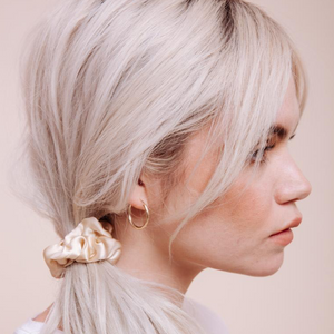 Close up side view of a model wearing a Cowgirl in the Sand Mini Scrunchie in a loose side ponytail