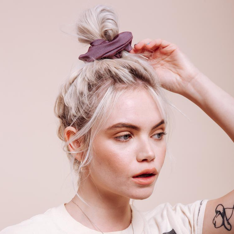 Purple Mauve Sweet Virginia Scrunchie styled in a messy top bun on a model close up