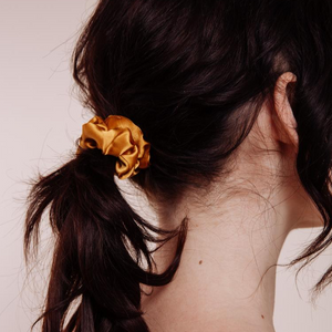 Close up rear view of a model wearing a Marigold Mini Scrunchie styled in a low ponytail at the back of her head