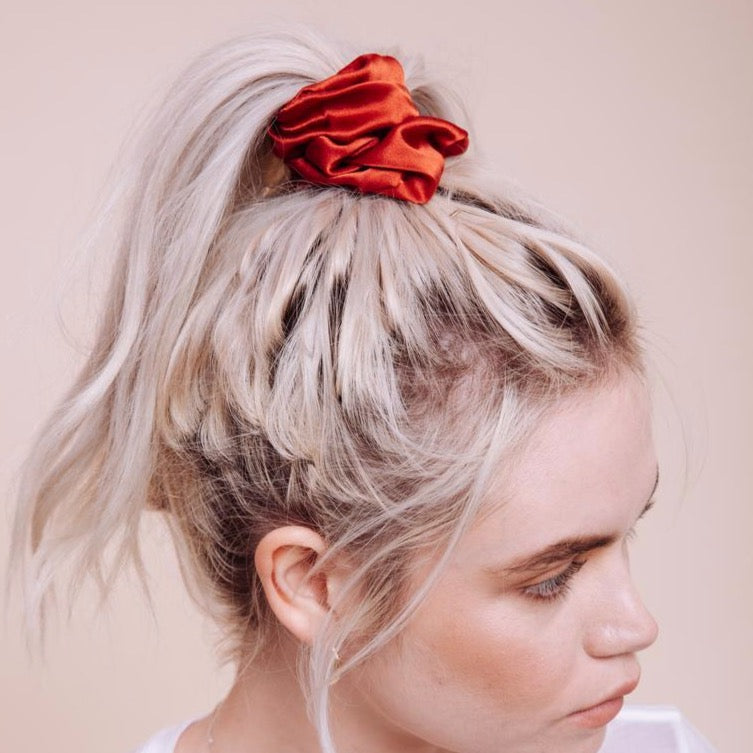 Close up view of Rusty orange colored Mojave Scrunchie styled in a high ponytail on a model