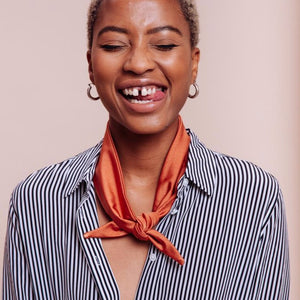 Close up of Tan Orange Phoenix Rising Scarf Tie around the neck of a model sticking her tongue out