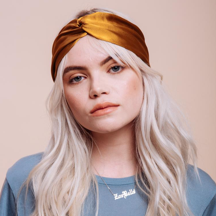 Front view close up of model wearing a Golden Canyon Turban Headband on her head over her hair