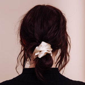 A back close up view of a model wearing a Cowgirl in the Sand Scrunchie in a low messy bun