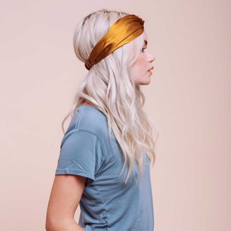 Side view of model wearing a Golden Canyon Turban Headband over her hair on her head