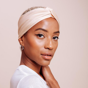 Side view close up of model wearing cream colored Milky Way Turban Headband from I'm With the Band laying flat