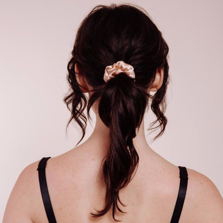 Back view of a model wearing Champagne Supernova Mini Scrunchie whic is champagne colored silk
