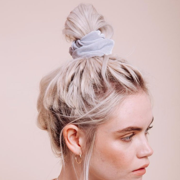 Light grey velvet Silverado Scrunchie styled on a model with a messy top bun close up side view